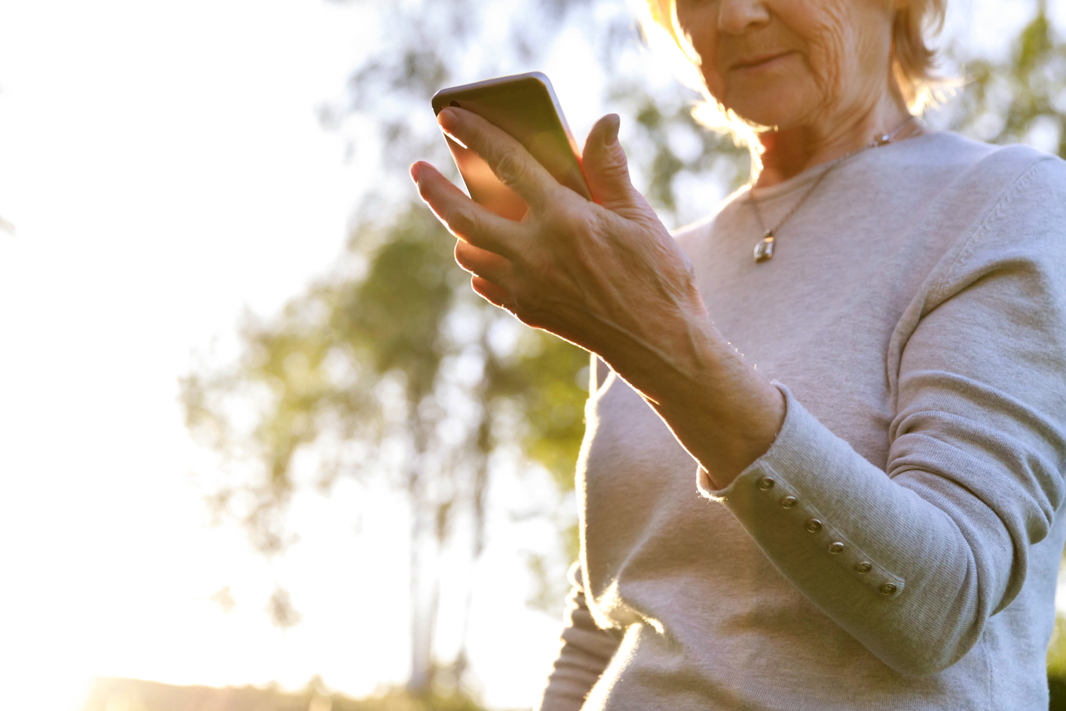 Elderly woman is holding a phone reading text
